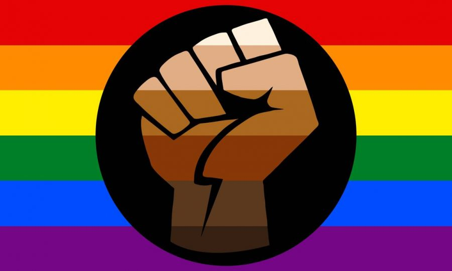 A fist colored in a gradient of different skin colors in front of a gay pride flag.