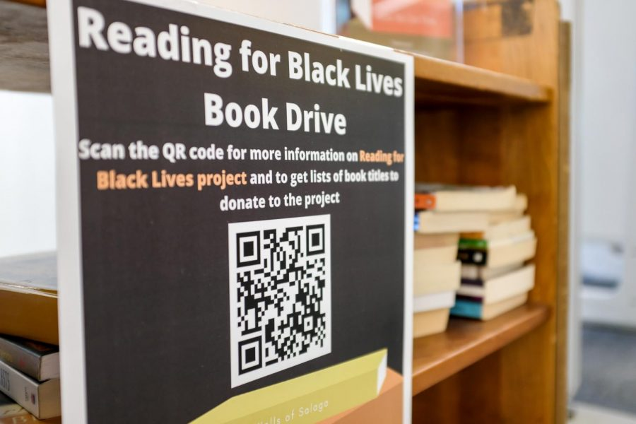 A shelf of books with a sign on it that says Reading for Black Lives Book Drive. Under this title text, there is a description that reads Scan the QR code for more information on Reading for Black Lives project and to get lists of book titles to donate to the project.