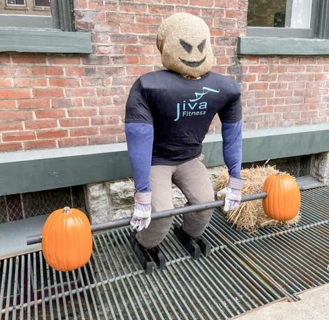 Scarecrow holding a barbell made of pumpkins.