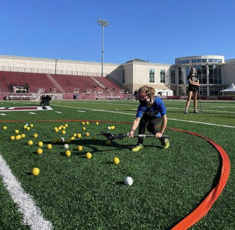 Elementary participant in Lafayette womens lacrosse teams free clinic successfully scooping a ground ball in Hungry Hippo drill. (Photo courtesy of @lafayette_wlax instagram)